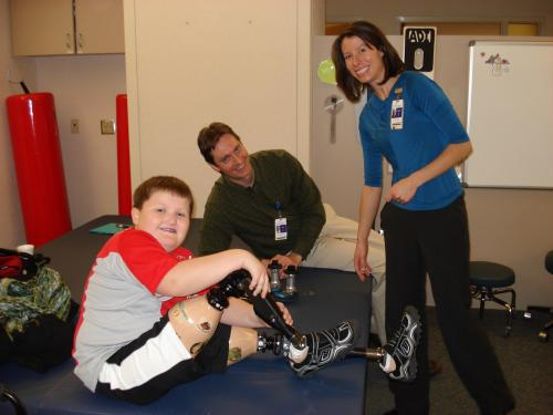 Nick and his new knees along with his prosthetists, John and Jen.