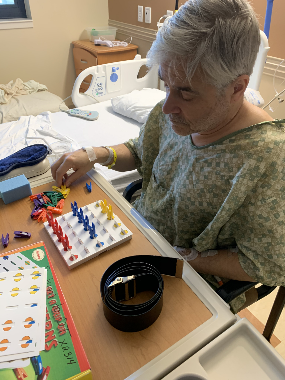 His OT says to put clips on corresponding colors. The left row is empty because he doesn't see that row. When he's finished, she moves the board a little to his right and he is stunned that another row was there all that time. This helps him start learning strategies to compensate for the loss.