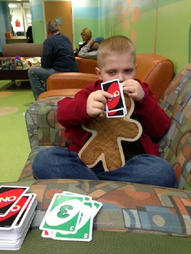 Carson and Gingerbread Batman playing UNO while waiting for an appt during our December visit to Memphis.