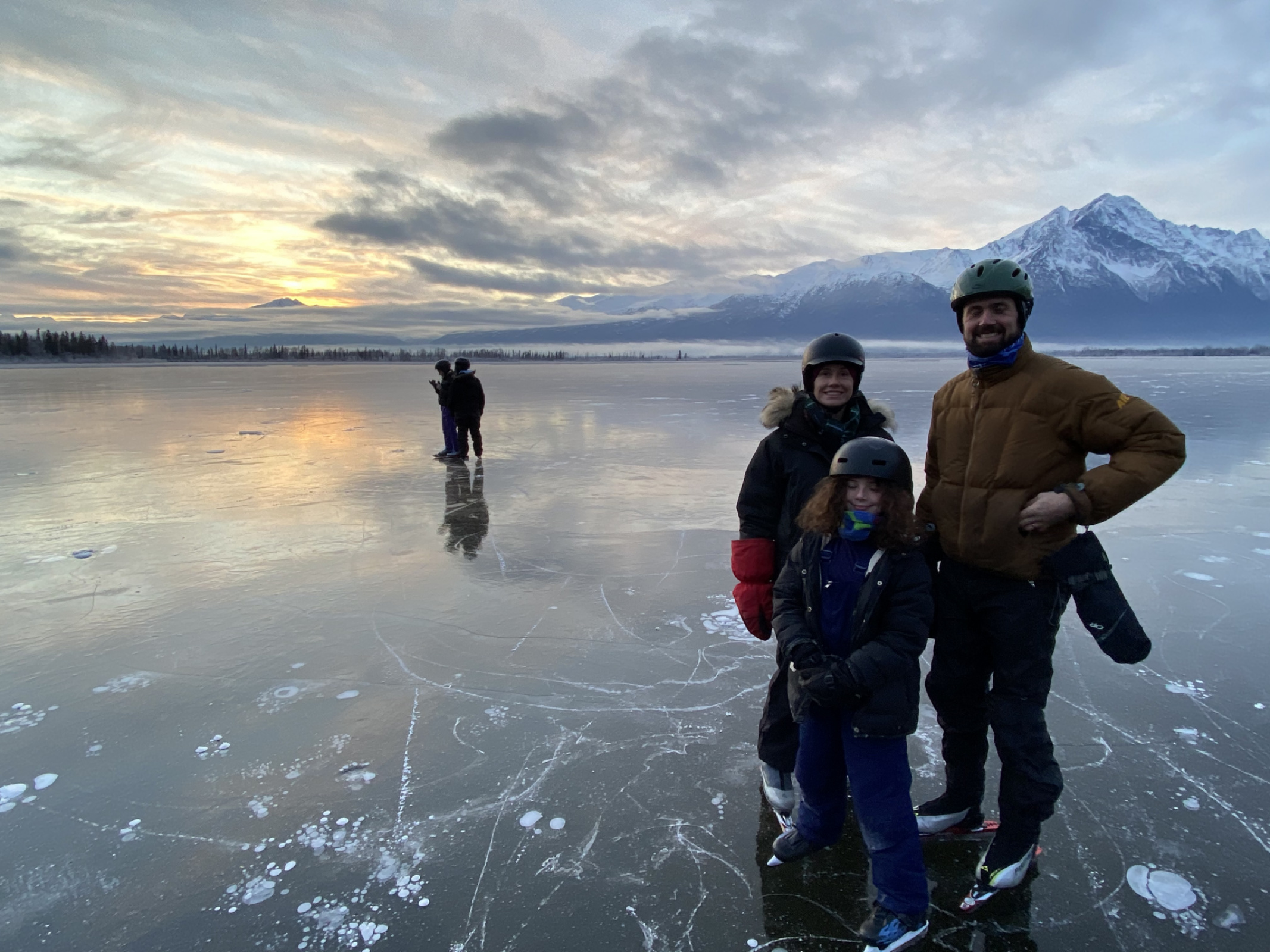 Holiday 2019 wild ice family skate with the Taygan family on Mud Lake, Knik River Valley.  We could see fish swimming under the ice.  My kids in the background looking at a phone, of course.