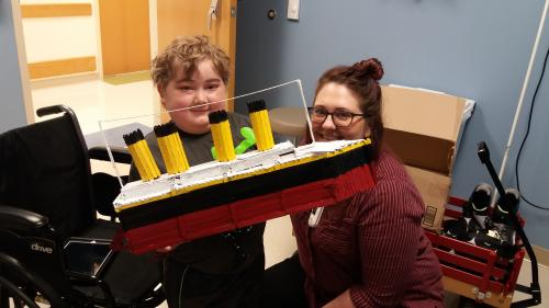 Samuel in clinic posing with his favorite art therapist, Cassie, and popsicle stick Titanic he built