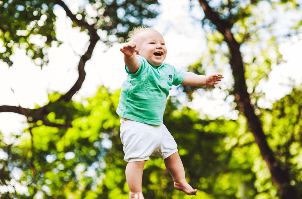 laughing baby getting tossed up in the air