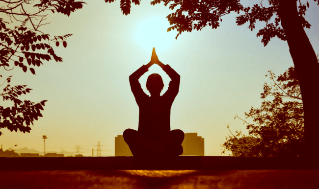 Caregiver sitting and doing yoga at sunset