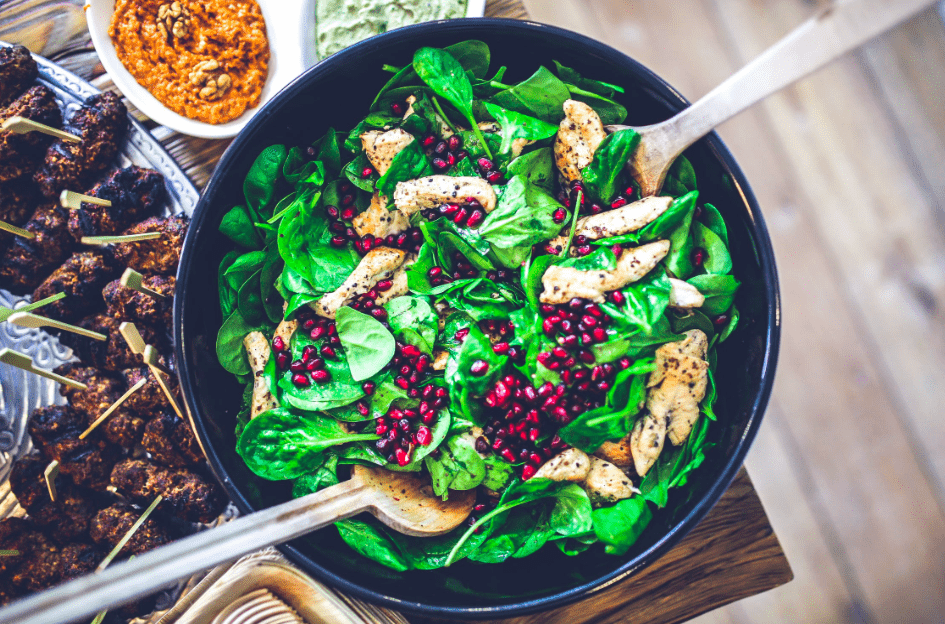 Healthy spinach salad with chicken and pomegranate seeds for caregivers