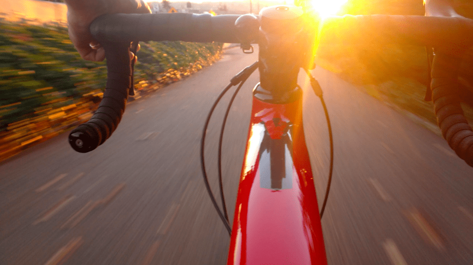 red bike from rider's perspective headed down a road