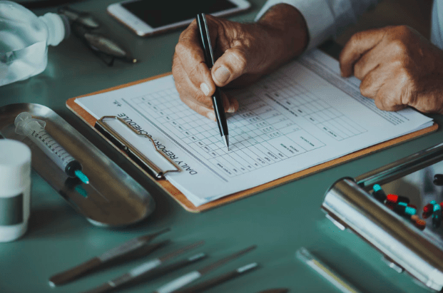 caregiver writing down medical notes on clipboard