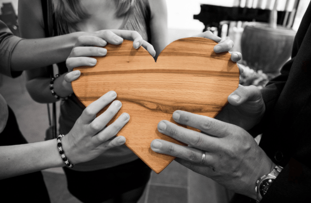 community of hands holding wooden heart