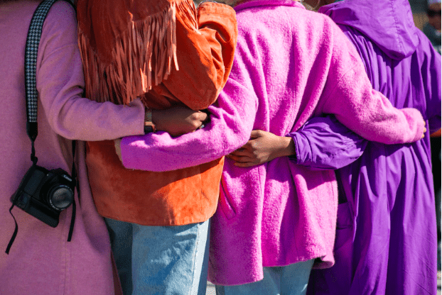 caregivers in pink and purple coats holding each others arms