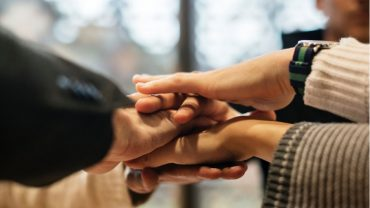 community of caregivers stacking hands