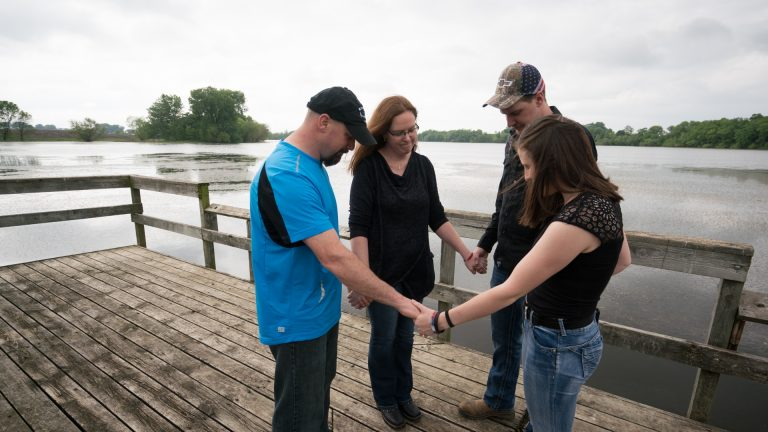 uicide attempt survivor Kevin Amundson prays with his parents and sister.