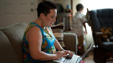 woman (Jen Ndegwa) types on a laptop